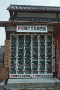 Vegetable vending machine is situated in front of a farm house.